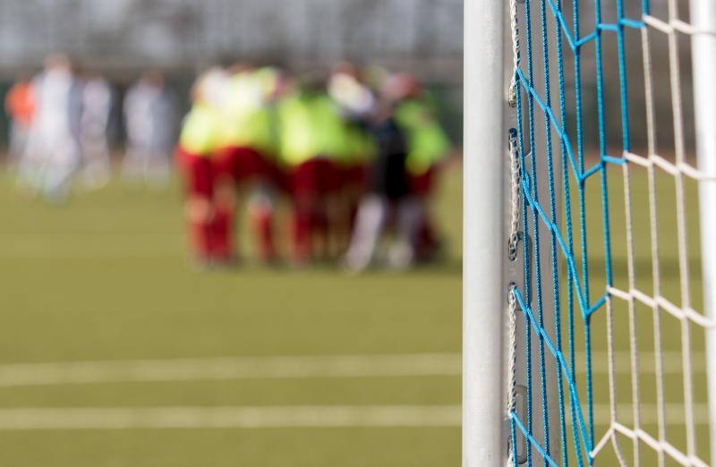 Eine Mannschaft steht hinter einem Fußballtor.